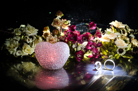 Wedding card, Wedding rings. Wedding bouquet, background. Flowering branch with white delicate flowers on wooden surface. Declaration of love, spring. Dark background with smoke and heart. Love conept