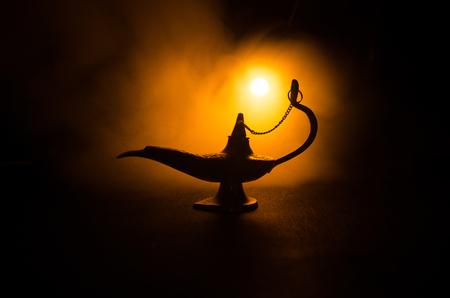 Antiguo Aladdin noches árabes genio estilo lámpara de aceite con suave luz humo blanco, fondo oscuro. Concepto de lámpara de deseos Foto de archivo