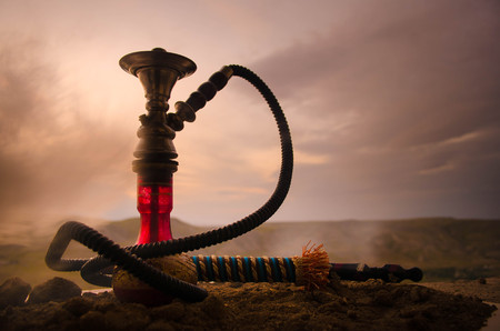 inhalation: Hookah, traditional arabic waterpipe, direct sunset light, outdoor photo. Mountain background Stock Photo
