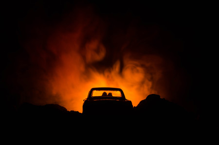 silhouette of car with couple inside on dark background with lights and smoke. Romantic scene