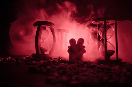 lighted: Time and love concept. Silhouettes of toy ceramic figures hugging between hourglasses in dark lighted background with fog. Couple love and time passes. Deadline of life