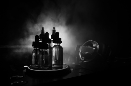 Vape and DJ Club concept. Smoke clouds and vape liquid bottles on Dj mixer close up. Light effects. Useful as background or vape or club advertisement