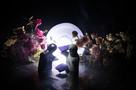 lighted: Two doll hugging on table with flowers and moon decoration Lighted background with smoke.Love concept. Greeting or gift card design idea. Silhouette of hugging couple