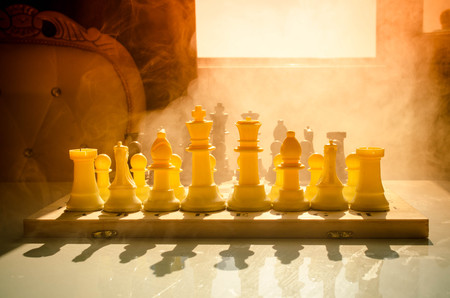 chess board: chess board game concept of business ideas and competition and strategy ideas concep. Chess figures on a dark background with smoke and fog. Selective focus