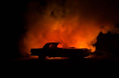sabotage: Burning car on a dark background. Car catching fire, after act of vandalism or road indicent. Burning vintage car nightshot