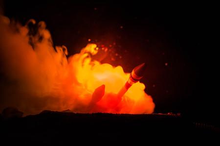 Lanzamiento de cohetes con nubes de fuego. Los misiles nucleares con la cabeza de guerra apuntaban al cielo sombrío en la noche. Rockets balísticos Guerra Backgound.