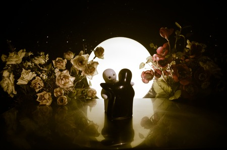 Two doll hugging on table with flowers and moon decoration Lighted background with smoke.Love concept. Greeting or gift card design idea. Silhouette of hugging couple