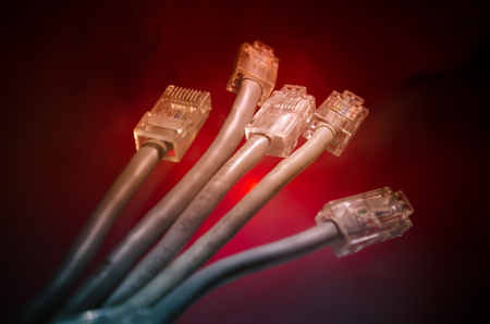Network switch and ethernet cables, symbol of global communications. Colored network cables on dark background with lights and smoke. Selective focus. Network internet concept background