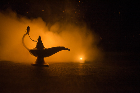 Antique arabian nights style oil lamp with soft light white smoke, Dark background. Lamp of wishes. Golden lamp. Toned 写真素材