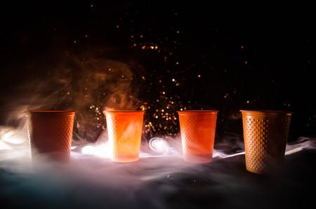 연기와 어두운 배경에 짚으로 오렌지 플라스틱 컵의 스택