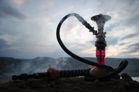 Hookah, traditional arabic waterpipe, direct sunset light, outdoor photo. Mountain background Stock Photo