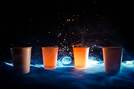 Stack of orange plastic cups with straw on dark background with smoke Stock Photo