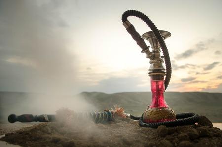 Hookah, traditional arabic waterpipe, direct sunset light, outdoor photo. Mountain background Standard-Bild