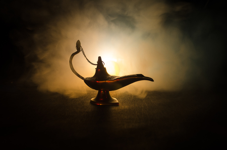 Antique arabian nights style oil lamp with soft light white smoke, Dark background. Lamp of wishes. Golden lamp. Toned Stock Photo