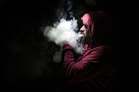 non violence: Vaping man holding a mod. A cloud of vapor. Black background. Vaping an electronic cigarette with a lot of smoke. Vape concept