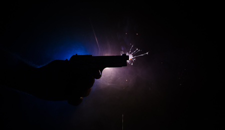 Male hand holding gun on black background with smoke ( yellow orange red white ) colored back lights Stock Photo