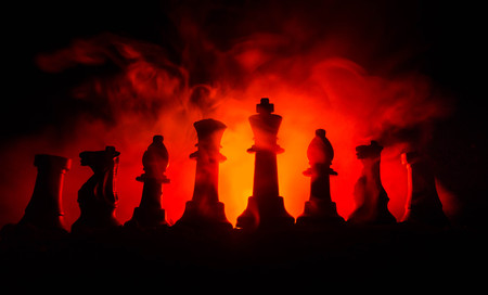 pensamiento estrategico: chess board game concept of business ideas and competition and strategy ideas concep. Chess figures on a dark background with smoke and fog. Selective focus