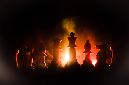 to contemplate: chess board game concept of business ideas and competition and strategy ideas concep. Chess figures on a dark background with smoke and fog. Selective focus