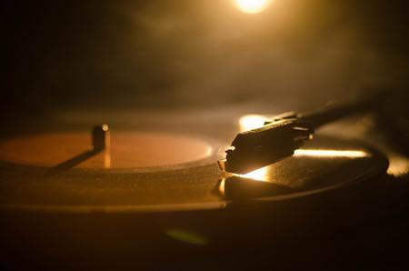 Turntable vinyl record speler. Retro audio apparatuur voor disc jockey. Geluidstechnologie voor DJ om muziek te mixen en afspelen. Vinyl plaat wordt gespeeld tegen brandende vuur achtergrond met rook Stockfoto
