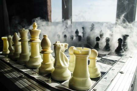 concep: chess board game concept of business ideas and competition and strategy ideas concep. Chess figures on a dark background with smoke and fog and window with sunlight. Selective focus