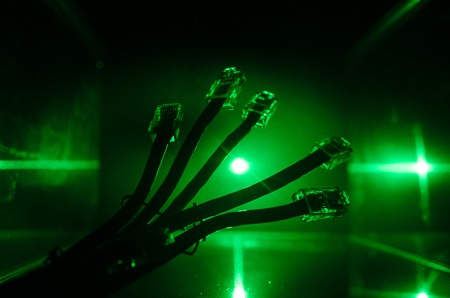 Conmutador de red y cables LAN, símbolo de las comunicaciones globales. Coloridos cables de red sobre fondo oscuro con luces y humo. Enfoque selectivo. Red de concepto de Internet de fondo Foto de archivo