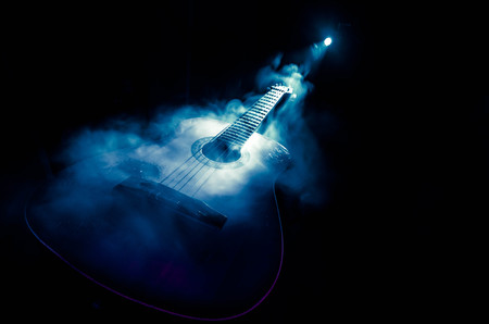 Music concept. Acoustic guitar isolated on a dark background under beam of light with smoke with copy space. Guitar Strings, close up. Selective focus. Fire effects. Surreal guitar