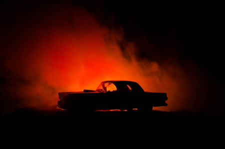 Burning car on a dark background. Car catching fire, after act of vandalism or road indicent. Burning vintage car nightshot