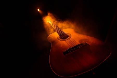 Concepto de la música. Guitarra acústica aislado en un fondo oscuro bajo el haz de luz con humo con copia espacio. Cuerdas de guitarra, de cerca. Enfoque selectivo. Efectos del fuego. Guitarra surrealista