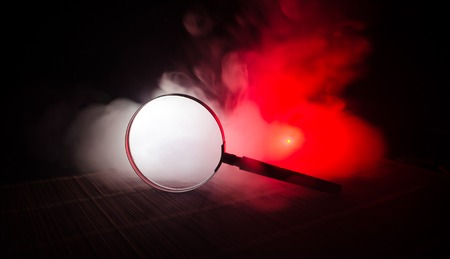 Close up Single Magnifying Glass with Black Handle, Leaning on the Wooden Table on orange red smoke dark background