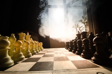 concep: chess board game concept of business ideas and competition and strategy ideas concep. Chess figures on a dark background with smoke and fog. Selective focus