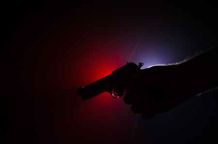 menace: Male hand holding gun on black background with smoke ( yellow orange red white ) colored back lights Stock Photo