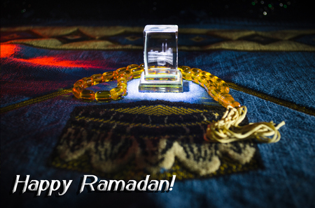 Holy Quran with beads on a prayer mat, Muslim Tasbih is a string of prayer beads which is traditionally used by Muslims along with the Quran. Ramadan holidays concept. Selective focus