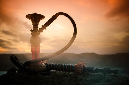 Hookah, traditional arabic waterpipe, direct sunset light, outdoor photo. Mountain background Archivio Fotografico