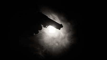point and shoot: Male hand holding gun on black background with smoke ( yellow orange red white ) colored back lights Stock Photo