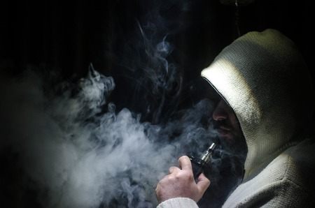 Liberando l'uomo in possesso di un mod. Una nuvola di vapore. Sfondo nero. Libera la sigaretta elettronica con un sacco di fumo. Vape concetto Archivio Fotografico - 81762817