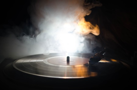 Turntable vinyl record player. Retro audio equipment for disc jockey. Sound technology for DJ to mix & play music. Vinyl record being played against burning fire background with smoke