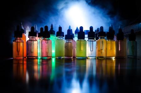 smoky black: Vape concept. Smoke clouds and vape liquid bottles on dark background. Light effects. Useful as background or vape advertisement or vape background.