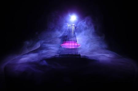 音楽のコンセプト。コピー スペースと煙と光のビームの下で暗い背景に分離されたアコースティック ・ ギターです。ギターの弦をクローズ アップ
