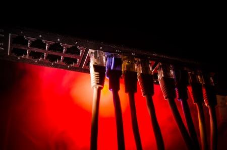 Conmutador de red y cables Ethernet, símbolo de las comunicaciones globales. Coloridos cables de red sobre fondo oscuro con luces y humo. Enfoque selectivo. Red de concepto de Internet de fondo
