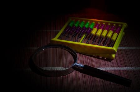 Chinese abacus and Magnifying glass on paper,business concept on a dark background