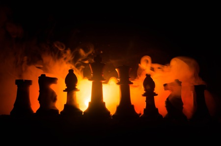 pawns: chess board game concept of business ideas and competition and strategy ideas concep. Chess figures on a dark background with smoke and fog. Selective focus