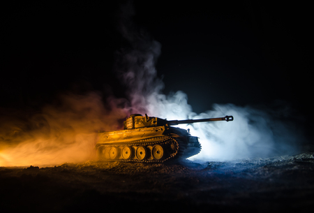 War Concept. Military silhouettes fighting scene on war fog sky background, German tank in action Below Cloudy Skyline At night. Attack scene. Armored vehicles. Tanks battle.