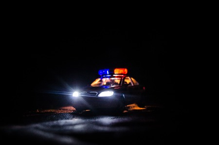 light duty: Police car chasing a car at night with fog background. 911 Emergency response police car speeding to scene of crime. Selective focus