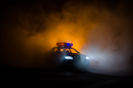 Police car chasing a car at night with fog background. 911 Emergency response police car speeding to scene of crime. Selective focus