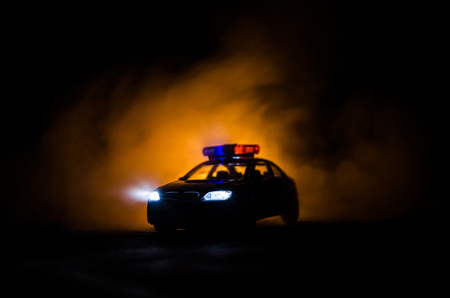criminal: Police car chasing a car at night with fog background. 911 Emergency response police car speeding to scene of crime. Selective focus
