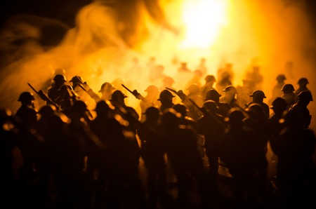 War Concept. Military silhouettes fighting scene on war fog sky background, World War Soldiers Silhouettes Below Cloudy Skyline At night. Attack scene. Stock Photo