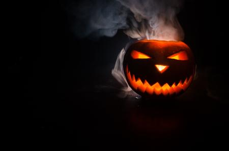 Halloween - old jack-o-lantern on black foggy background. Closeup of scary halloween pumpkins