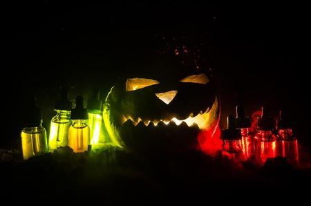Colorful vape liquids with Halloween pumkin on dark background. Vape Halloween party or vape promo concept on Halloween holidays promo Stock Photo