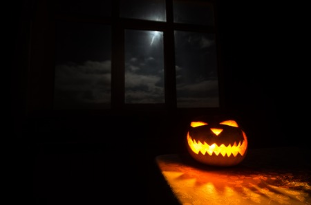 Scary Halloween pumpkin in the mystical house window at night or halloween pumpkin in night on room with blue window.