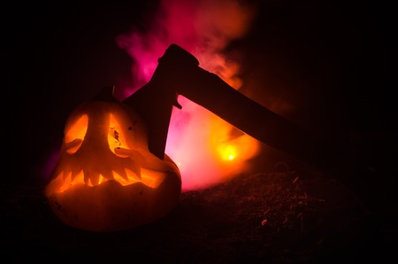 Scary orange pumpkin with carved eyes and a smile with burning candles and an ax on a dark background with fire sky.